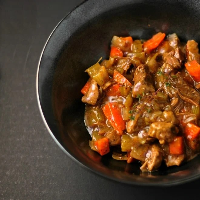A black bowl sitting on a dark gray background. The bowl is full of classic beef stew that is shiny and full of orange carrots