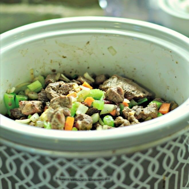 A photo of beef, celery, carrots and the other ingredients all loaded into the crockpot ready to make into classic beef stew