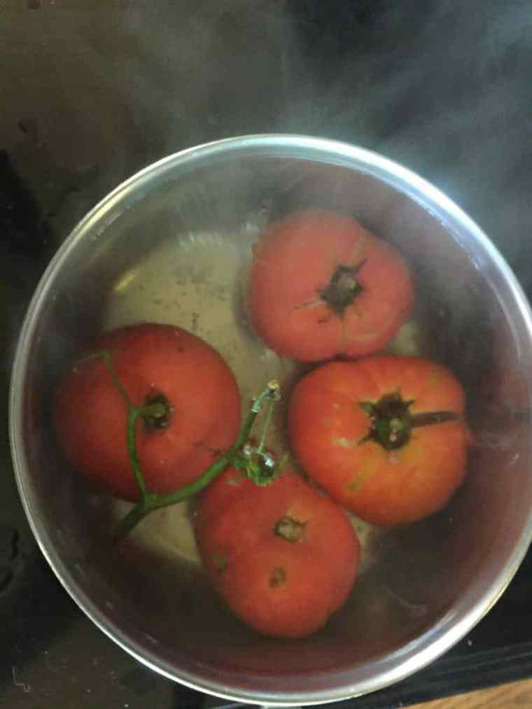 Four whole tomatoes in boiling water in stock pot
