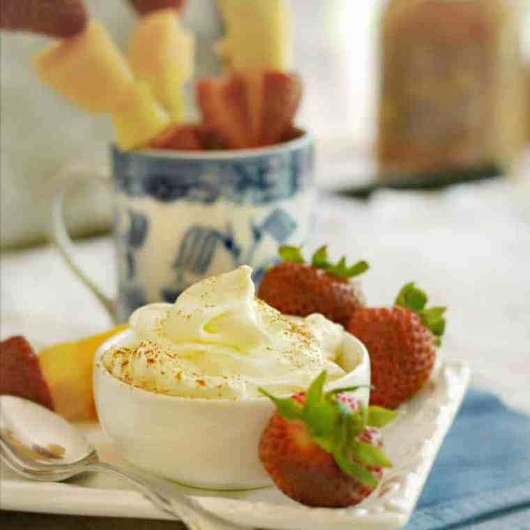 white bowl of fruit dip with strawberries and a spoon