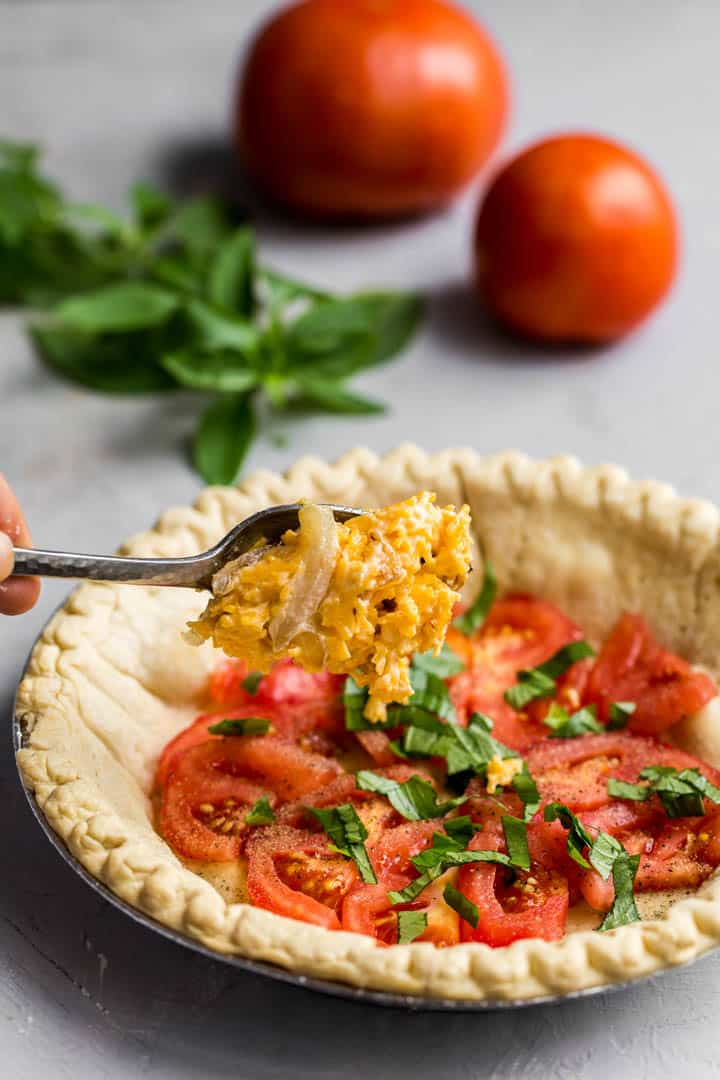 parbaked pie shell with layer of tomatoes, herbs and cheese mix being spooned on.