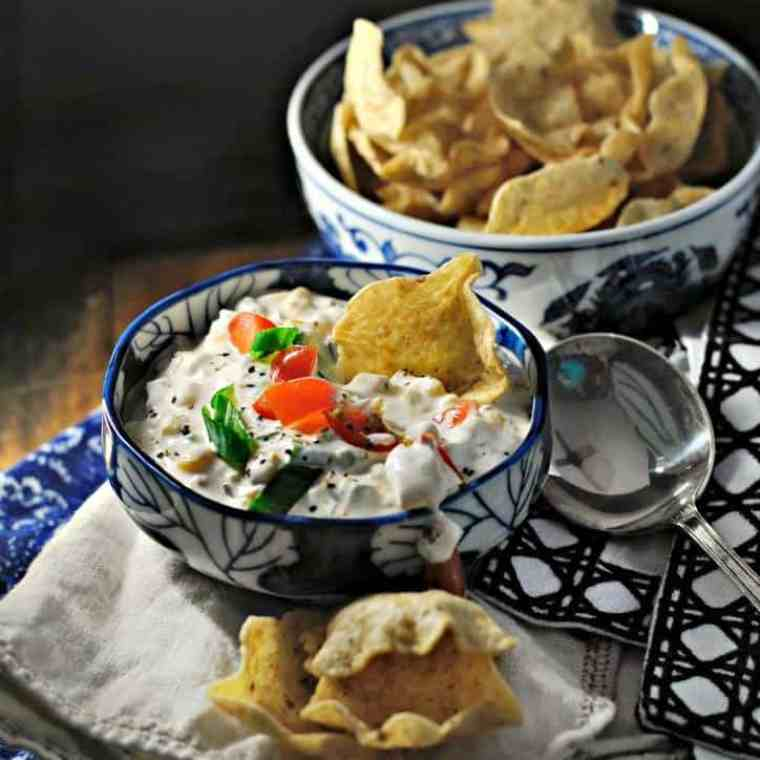 Blue bowl of corn dip with scooping chips, blue napkins