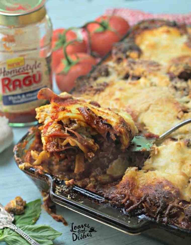 A photo of the lasagna being scooped out with the empty sauce jar in the background Cowboy Lasagna www.loavesanddishes.net