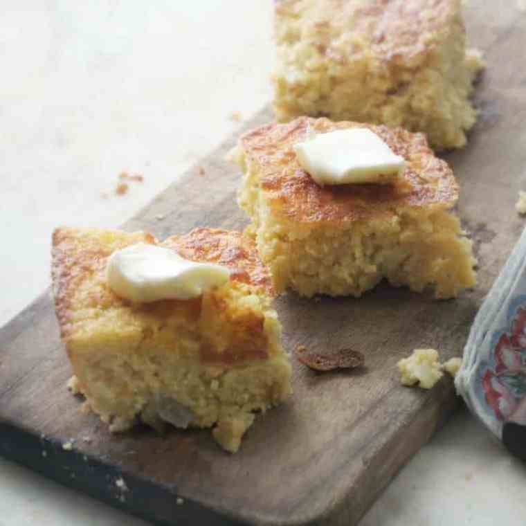 Southern Mexican Cornbread with butter on top and sitting on a cutting board - view from the side