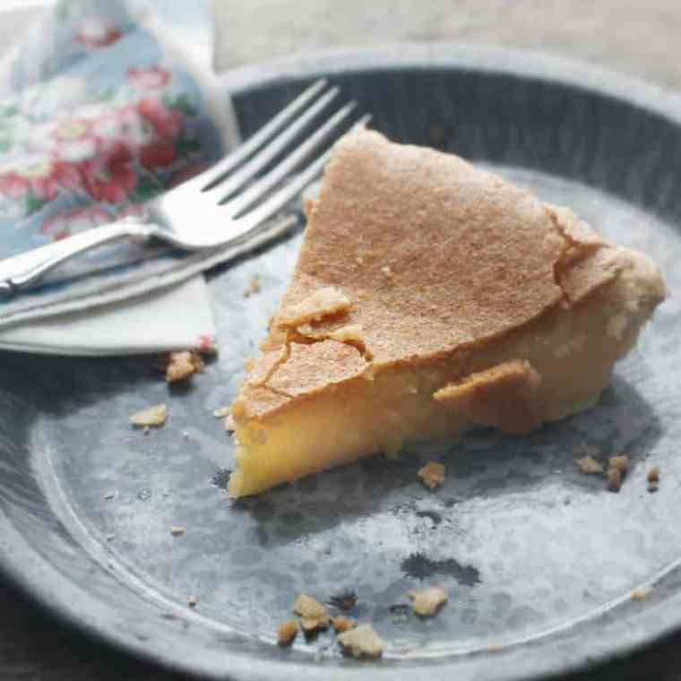 A slice of Pie sitting on a graniteware plate with flowered napkin and fork
