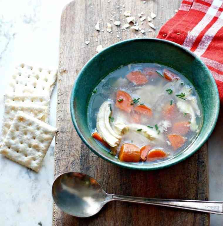 green bowl of soup with crackers and spoon