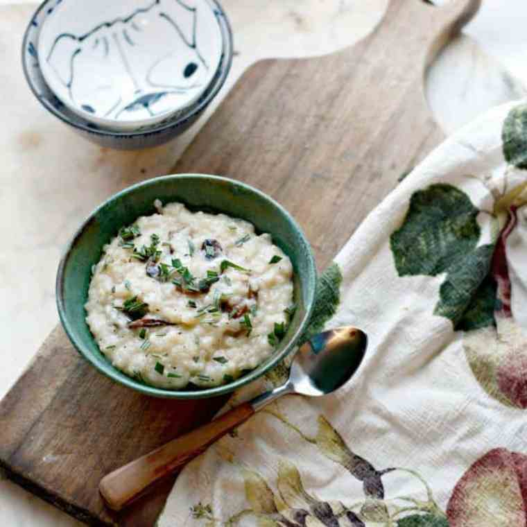 a photo of Creamy No Stir Parmesan Mushroom Risotto overhead and at a distance with a towel and spoon and bowls in the frame