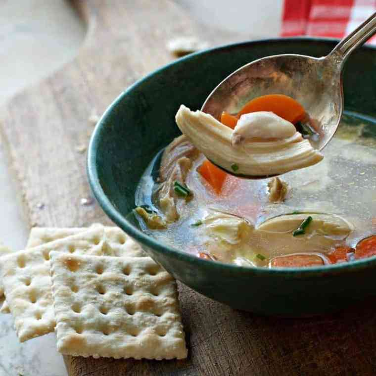 A photo of a spoonful of chicken meat in chicken soup