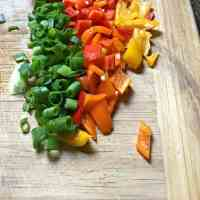 A photo of four colors of chopped peppers cut up on the cutting board - green, red, yellow and orange