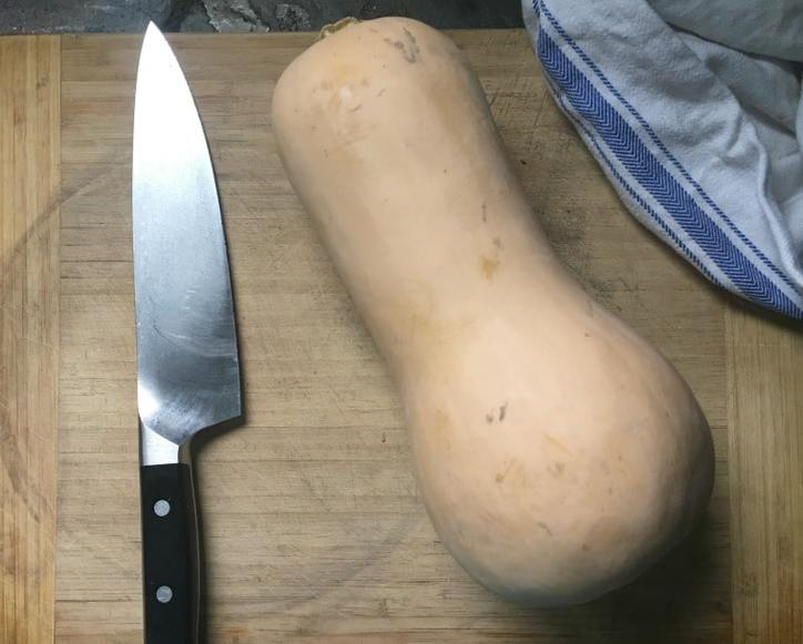 A photo of a butternut squash and a knife on a cutting board.