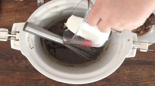 Pouring cornstarch slurry out of a glass measure to the drippings to make a gravy in the crockpot with whisk in the back ground FOR ALL THE SECRETS TO PERFECT CROCKPOT POT ROAST