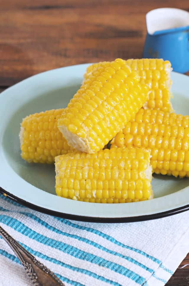 A plate of yellow corn on the cob sitting on a blue plate