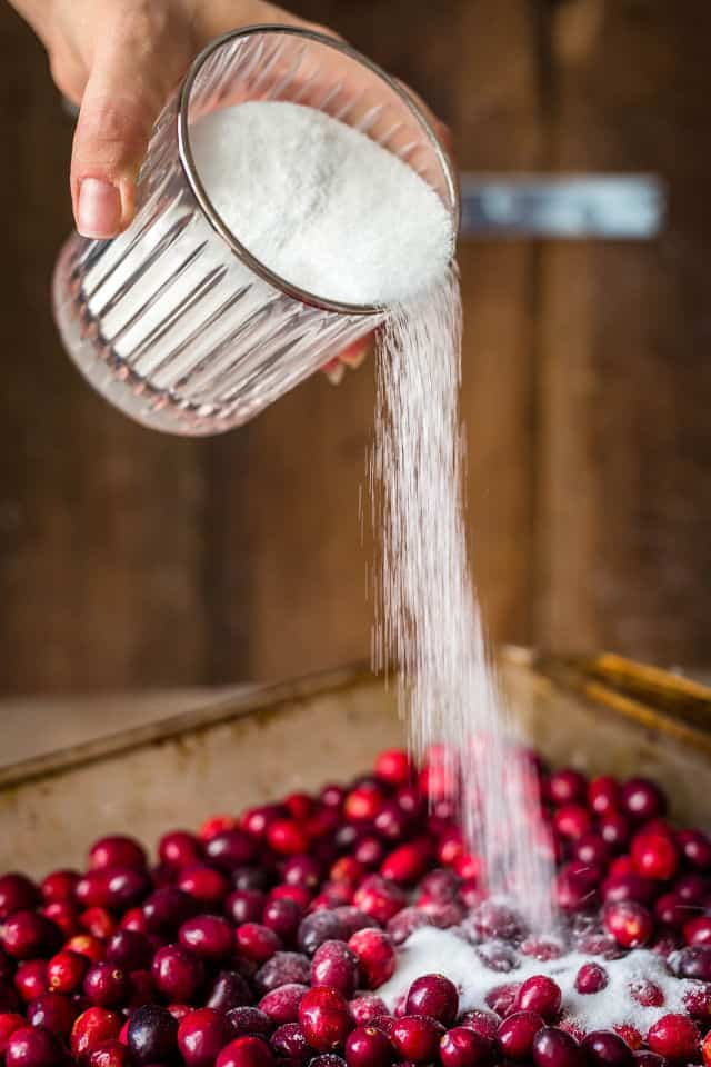 White sugar being poured over the cranberries in the pan