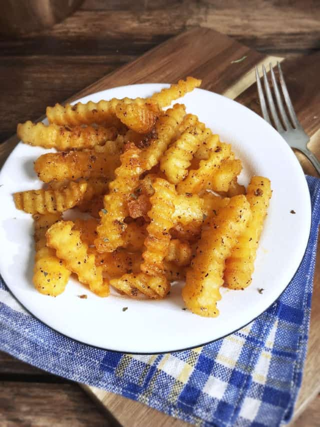 Golden crinkley fries on a white plate with blue napkin