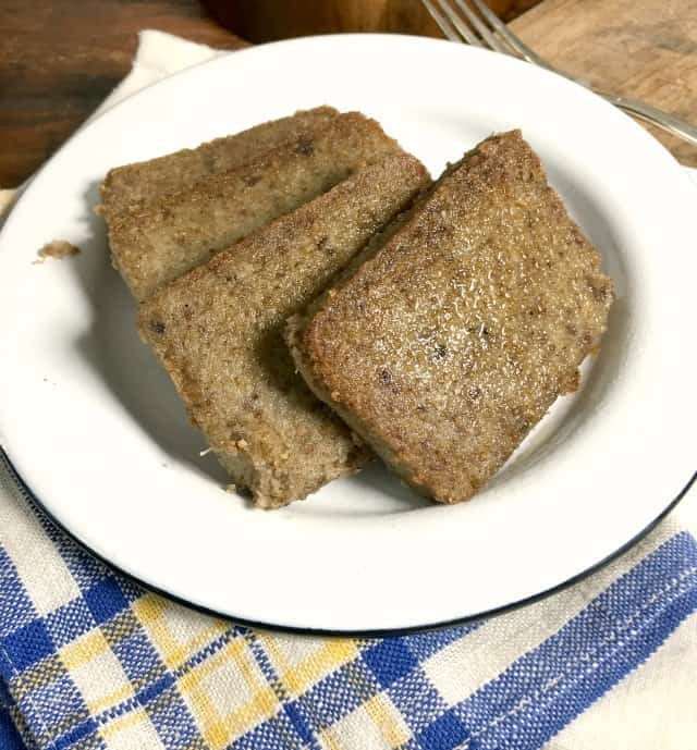 four slices of scrapple on white plate with blue, white and yellow napkin