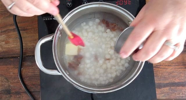 a photo of adding all ingredients to the saucepan for how to cook canned hominy