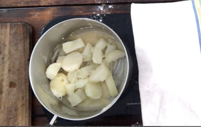 Potatoes and roux in a sauce pan with towel