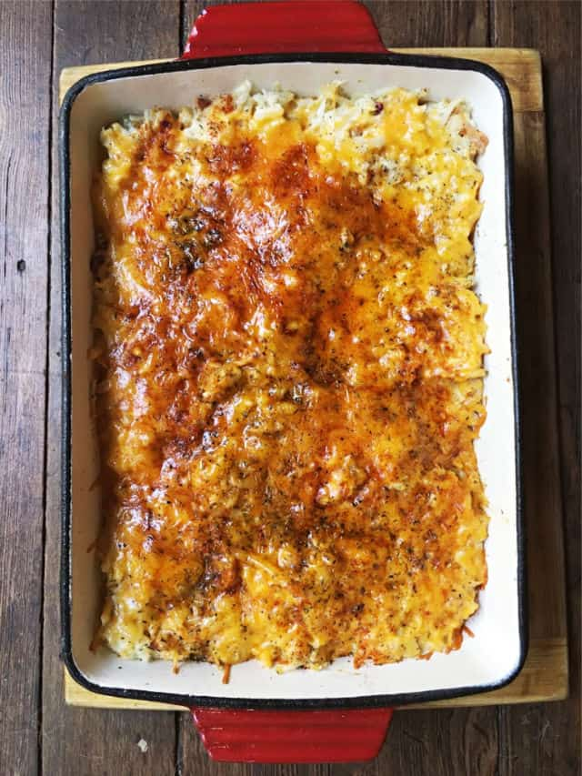 a baked cheesy top of hashbrown casserole in red dish