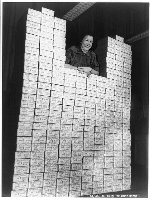 Woman posed with stack of packages of $1 silver certificates at the Bureau of Engraving and Printing, Washington, D.C.