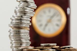 a stack of coins with a clock on the background