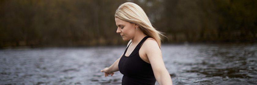 blonde-woman-wearing-black-walking-into-loch