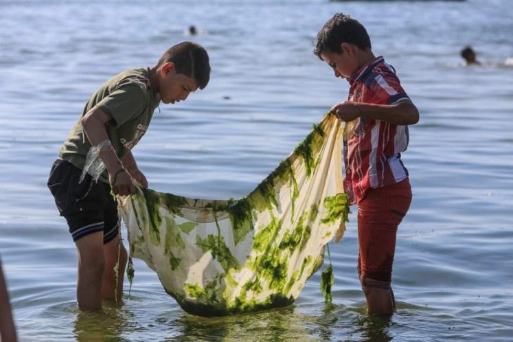 Twee Palestijnse jongens proberen wat vis te vangen aan de kust van Gaza