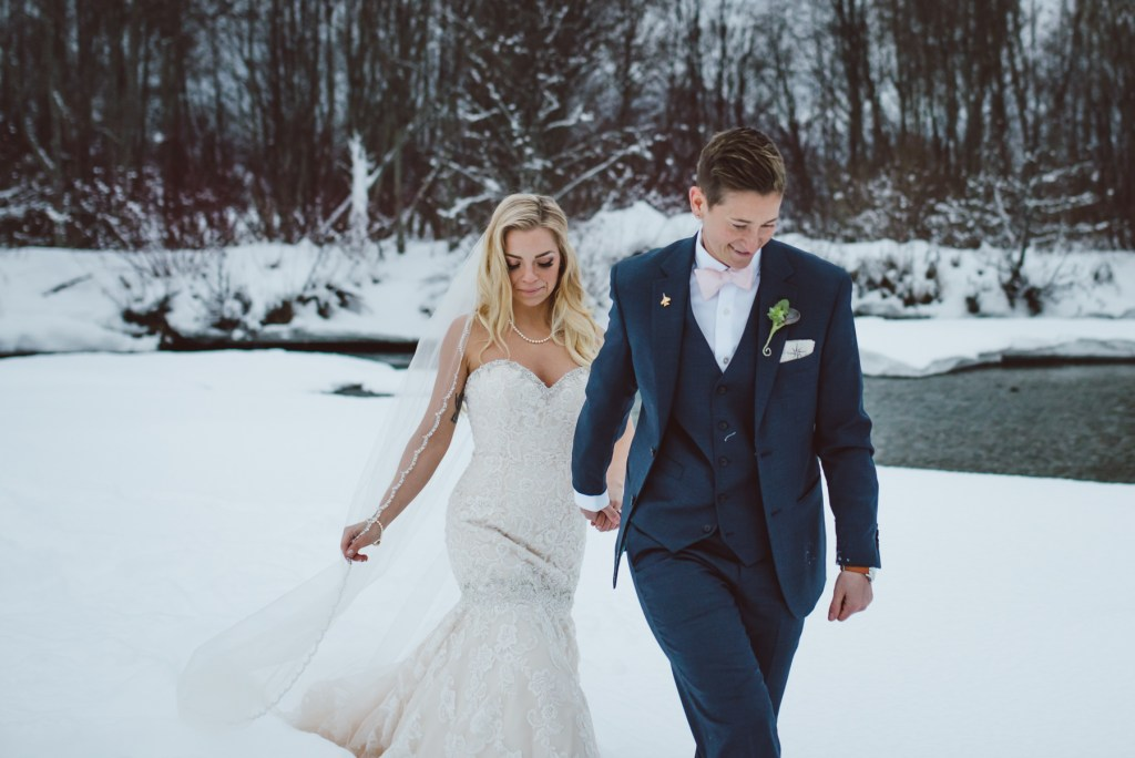 same sex couple walk in the winter forest