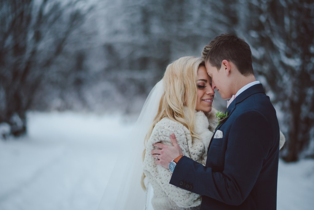 same sex couple embrace in the winter forest
