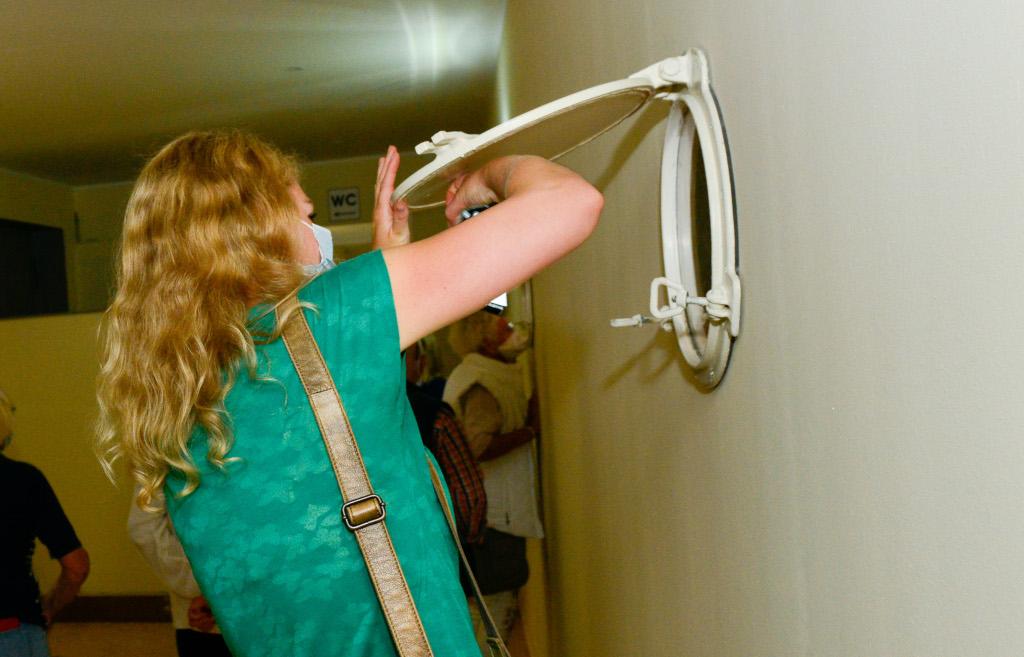 Eine Frau hebt die Klappe von einem weißen Bullauge in einer Wand an und fotografiert dadurch.