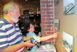 """Bob Carney, exhibit volunteer, and Sarah Baylinson, museum manager, hang the """"Bridging the Gap"""" photo exhibit at Hotwire."""