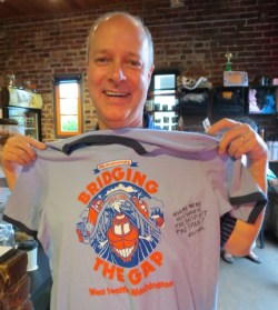 """Rob Shiras, owner of IT Headquarters, shows off his """"Bridging the Gap"""" T-shirt, inscribed by the artist Dave Kelliher with the question """"Where you were you when the ship hit the span?"""""""
