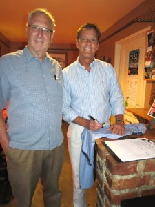 """Dick Sherman (left), ad representative for Robinson Newspapers, has his """"Bridging the Gap"""" T-shirt inscribed by artist David Kelliher during the June 12, 2014, debut of the shirts at Hotwire Online Coffeehouse."""