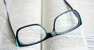 óculos em cima de livro ou dicionário- gerenciamento de alarmes