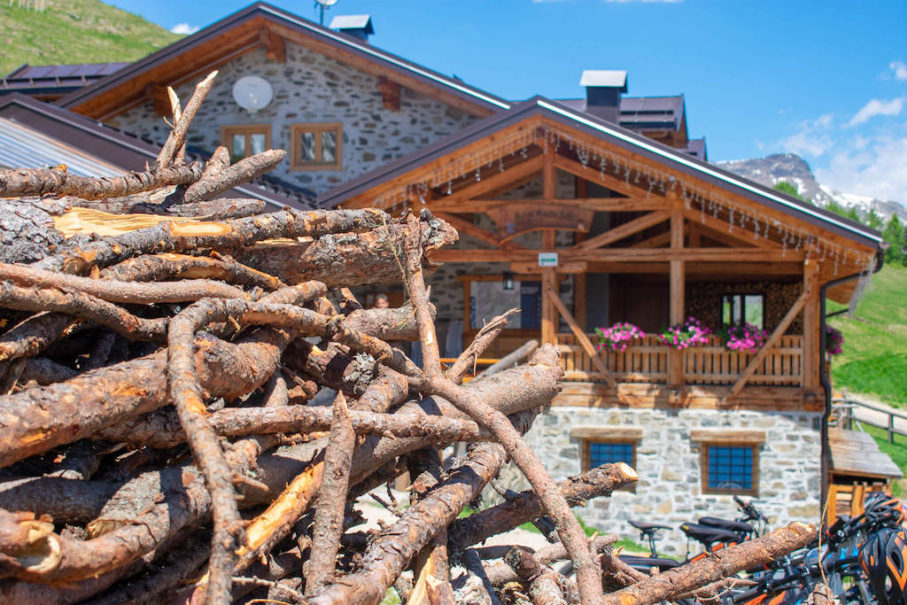 Visit Trentino Italy - wooden alpine lodge in mountains with firewood in foreground
