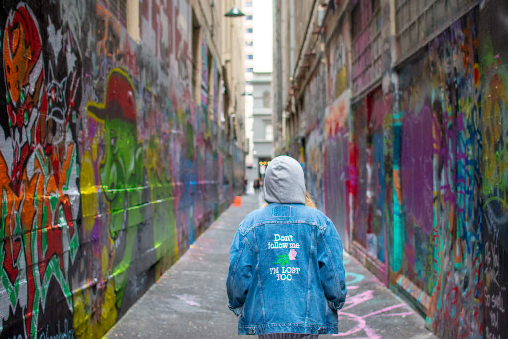 Melbourne street art, girl standing in graffiti covered alleyway