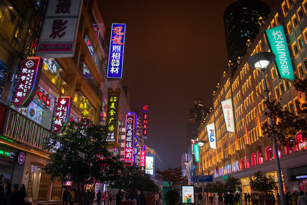 Shanghai Nanjing Road East, busy street at night with large buildings and lots of bright neon lights