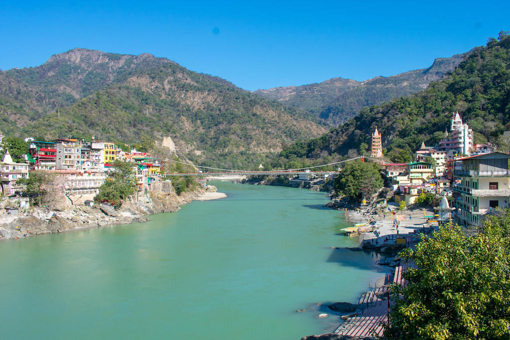 Rishikesh spread over two sides of the Ganga River in North India with mountains in background