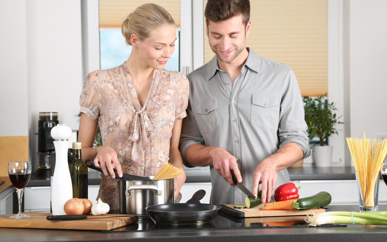 Couple cooking at a virtual cooking class, at home date night ideas