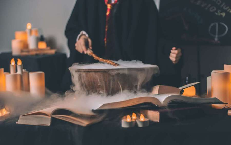 Cauldron surrounded by books and candles