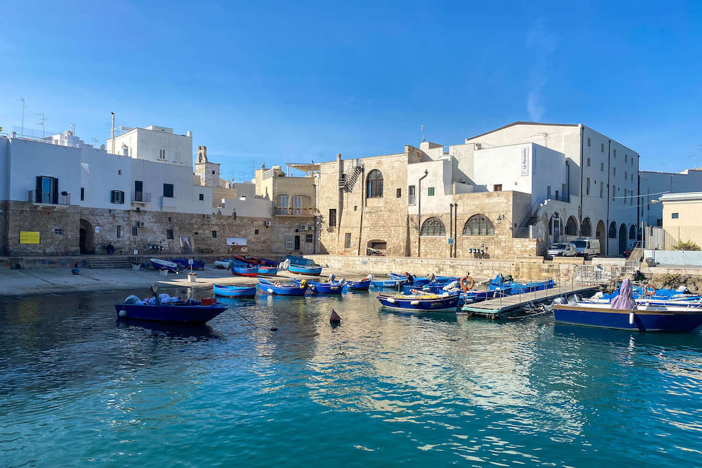 The port of Monopoli with little blue and red boats floating on turquoise waters, best places to visit in Puglia