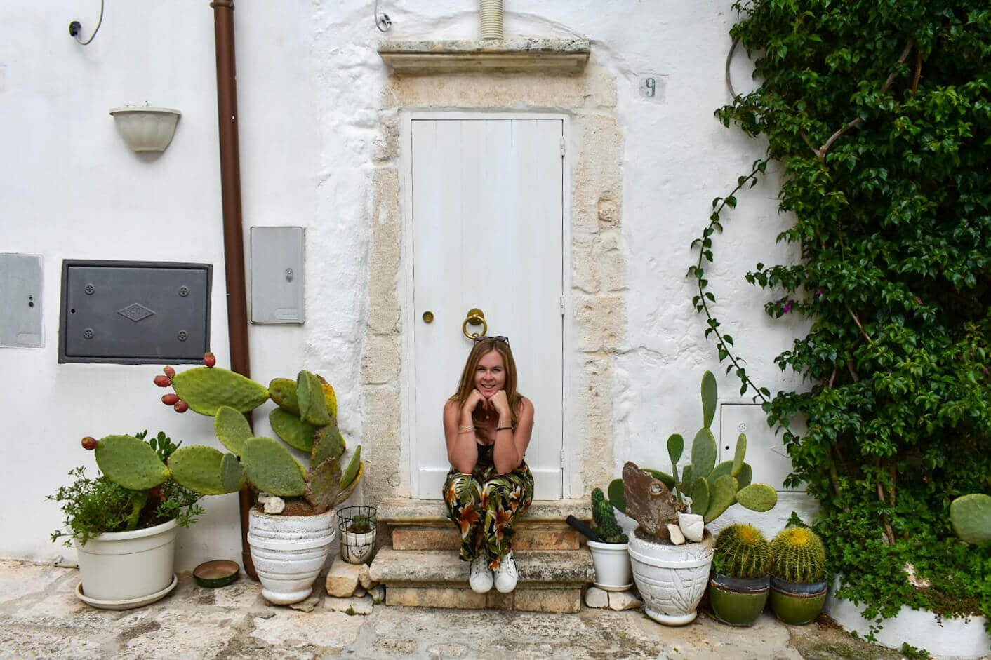 Girl sitting on doorstep surrounded by cacti in Ostuni Italy