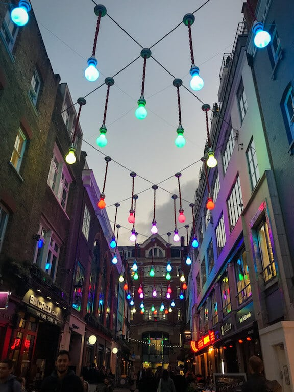Carnaby London colourful lightbulb lights hanging above street by night