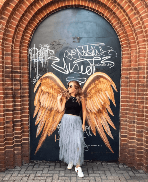 Girl in front of wings mural in Shoreditch