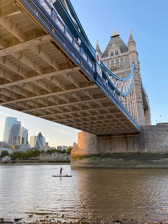 Person stand up paddle boarding under Tower Bridge in London