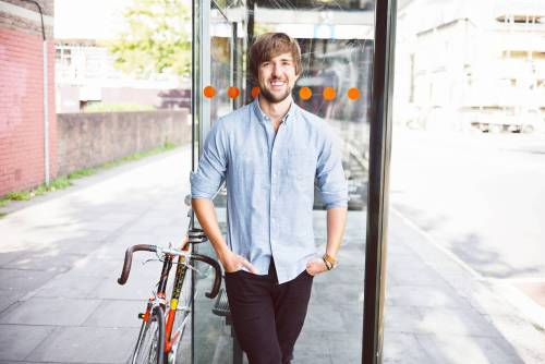 Andreas leaning against a bus stop with his bike on the left