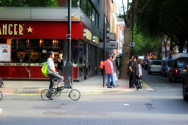 A Brompton cyclist waits at a red light