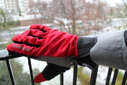 Red Sealskinz winter cycling glove on a snowy backdrop