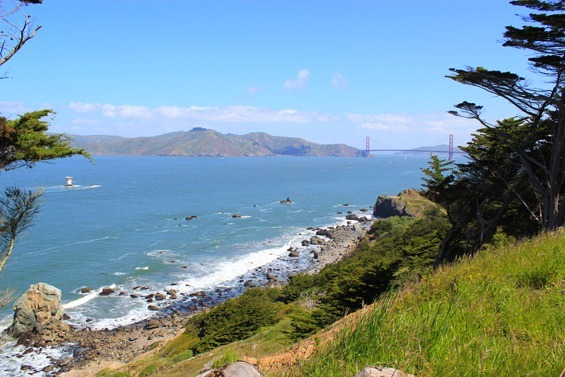 View of Golden Gate Bridge as well as the beautiful blue coastline with waves crashing into the rocks below