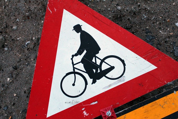 A sign of a cyclist on a Dutch style bike lies on the ground in Copenhagen
