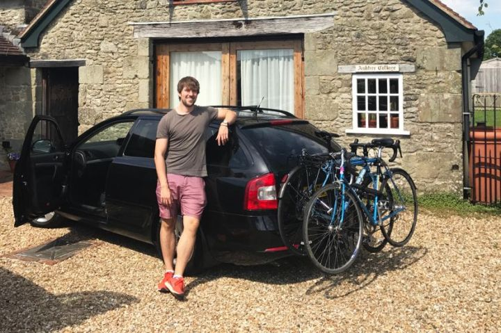 Man stood next to car with a bike rack on the back near a cottage